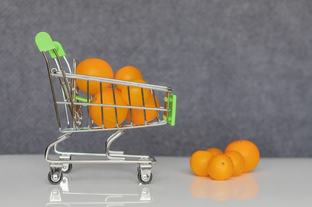 Green shopping cart with yellow cherry tomatoes.