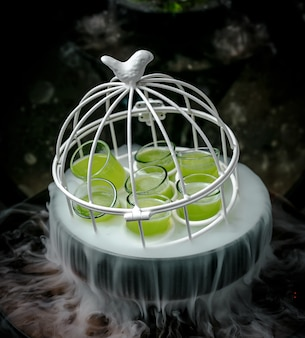 Green shots in white small cage in smoky bowl