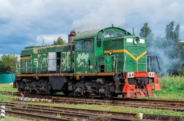 Зеленый маневровый локомотив на железнодорожных путях