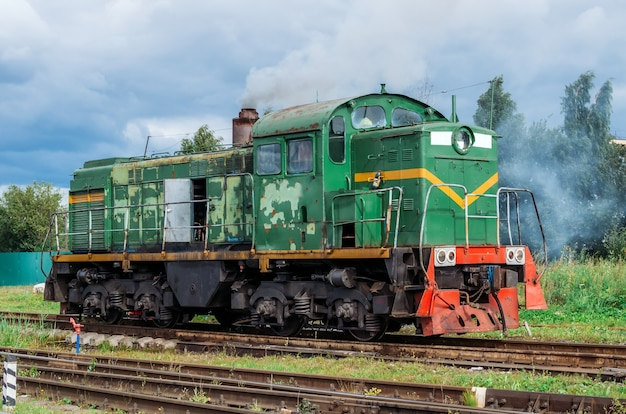 Green shunting locomotive on railway tracks