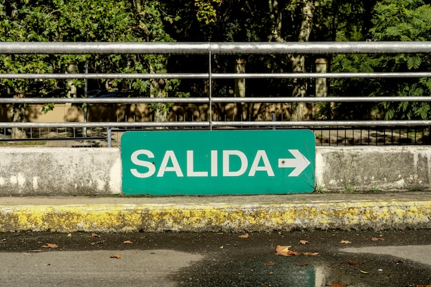 Green sign that says exit in spanish in a parking lot.