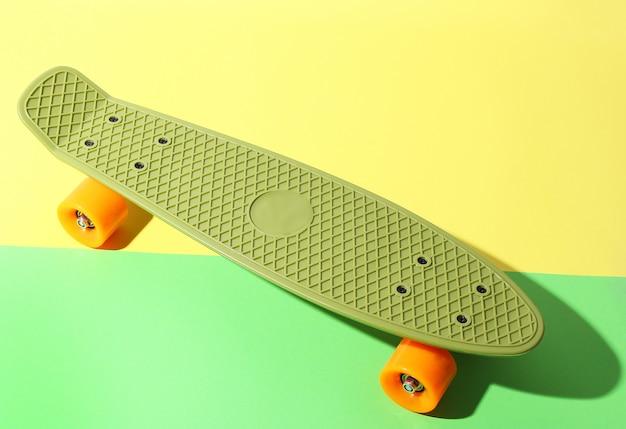 Green skateboard with orange wheels on yellow and green. plastic mini cruiser board.