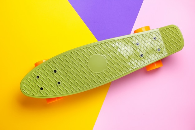 Green skateboard with orange wheels on yellow, purple and pink. plastic mini cruiser board.