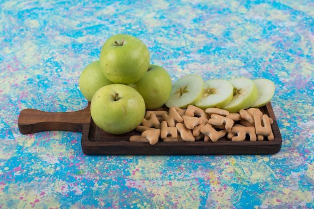 中央に木の板にクラッカーと緑のスライスしたリンゴ。