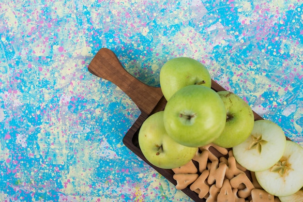 Green sliced apples with crackers on the wooden board on blue.