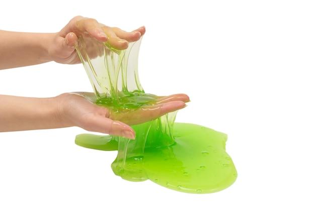 Игрушка зеленой слизи в руке женщины изолированной на белой предпосылке.