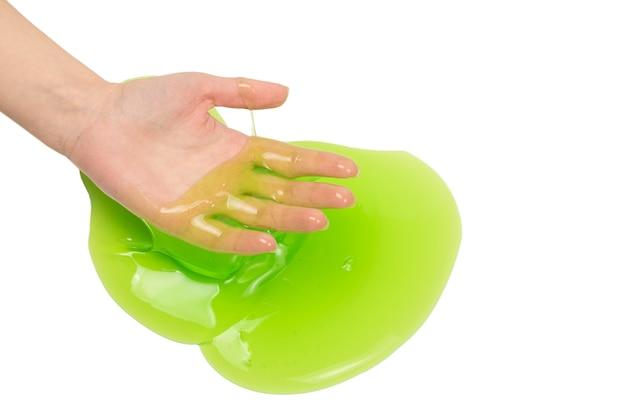 흰색 배경에 고립 된 여자 손에 녹색 점액 장난감.