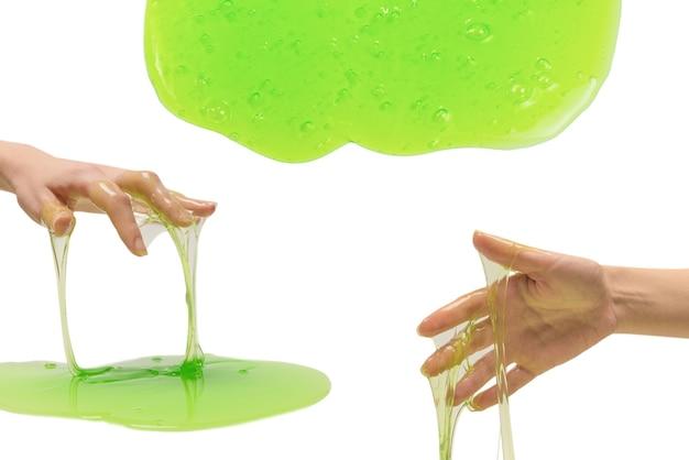 白い表面で隔離の女性の手で緑のスライムのおもちゃ。