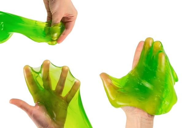 白で隔離される女性の手で緑のスライム グッズ。上面図。