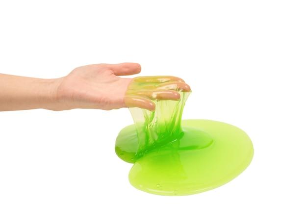 白で隔離の女性の手で緑のスライムのおもちゃ