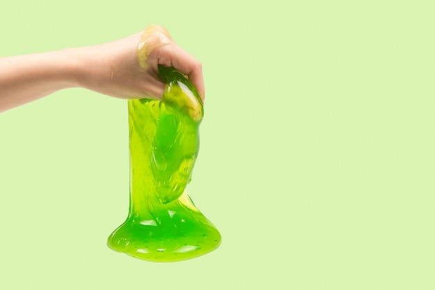 여자 손에 흰색 절연 녹색 점액 장난감.