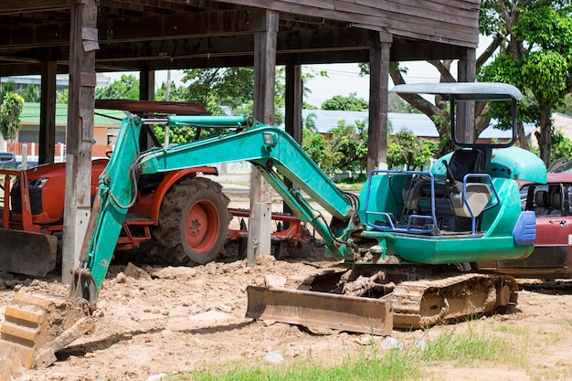 Green small excavators working in construction area
