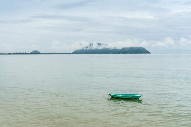 Green small fishng boat parked at the shore of prachuap bay with fog on khao ta mong lai forest park background, thailand