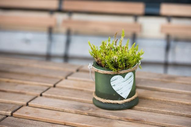야외 카페의 테이블에 꽃과 하트가 있는 녹색 작은 냄비