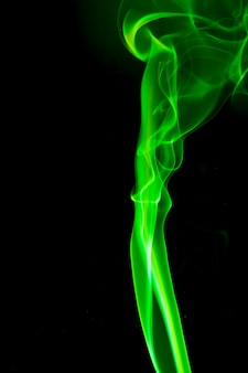 Green smoke on black surface.
