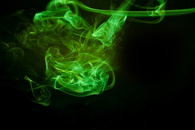 Green smoke motion on black surface.