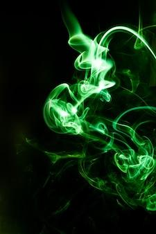 Движение зеленого дыма на черном фоне.