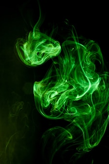 黒の背景に緑の煙の動き。