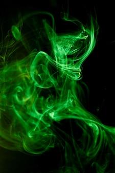 Движение зеленого дыма на черной поверхности.