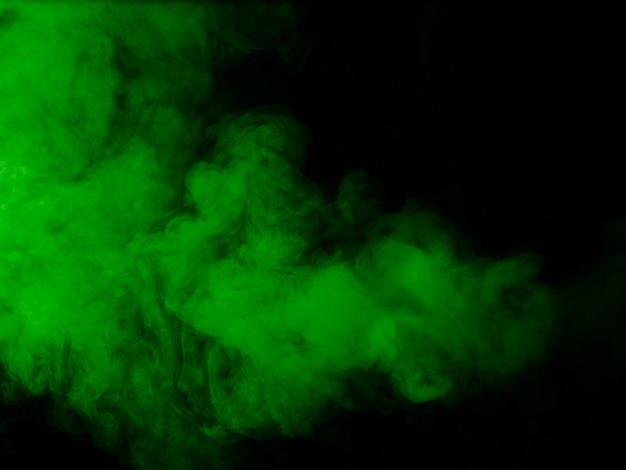 黒の背景に緑の煙