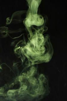 Il fumo verde turbina sullo sfondo nero