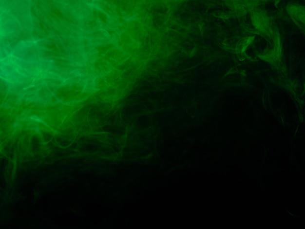 黒の背景に緑の煙のテクスチャ