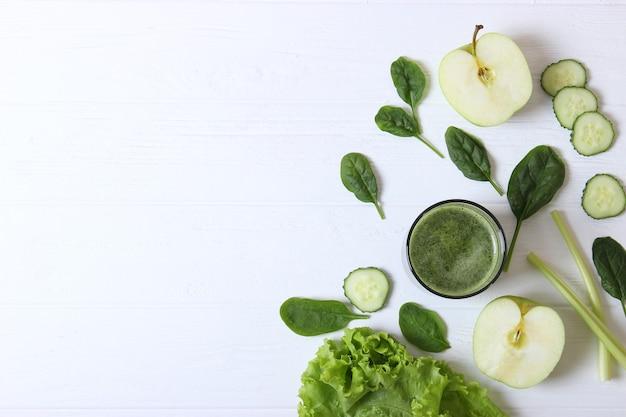 해독 유기체를 위한 탁자 위에 있는 녹색 스무디와 신선한 야채