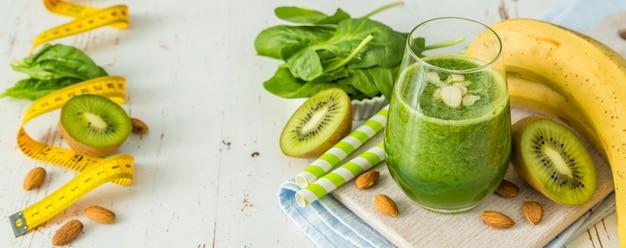 Зеленый коктейль и ингредиенты на белом фоне