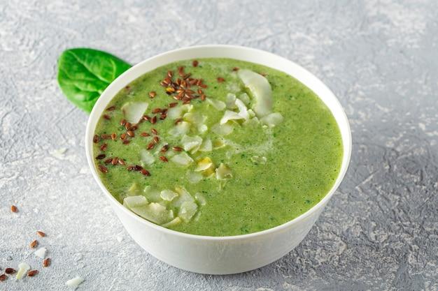 ほうれん草、アボカド、セロリ、キウイ、ココナッツミルクのグリーンスムージーボウル、ココナッツフレーク、亜麻仁を添えて