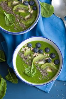 Зеленый смузи в миске со шпинатом киви черника лайм банан с семенами чиа