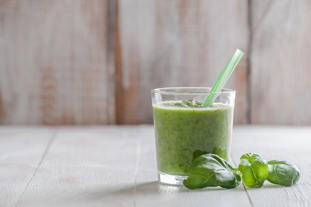 Зеленый коктейль из разных овощей и фруктов на деревянном столе. здоровое питание для долгой жизни