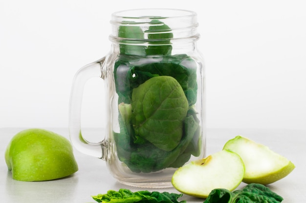 Green smoothie in glass jar with fresh organic green vegetables and fruits on grey background. spring diet, healthy raw vegetarian, vegan concept, detox breakfast, alkaline clean eating. copy space.