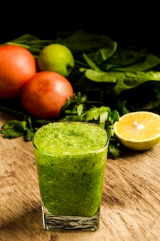 Green smoothie in glass with lemon