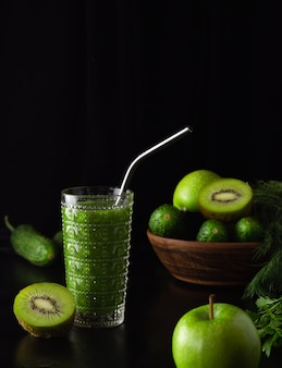 검정색 배경에 유리잔에 그린 스무디. 키위, 사과, 오이, 채소. 건강 식품 요리. 제로 웨이스트, 금속 튜브.