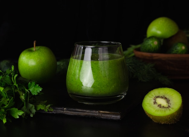 검정색 배경에 유리잔에 그린 스무디. 키위, 사과, 오이, 채소. 건강 식품 요리.