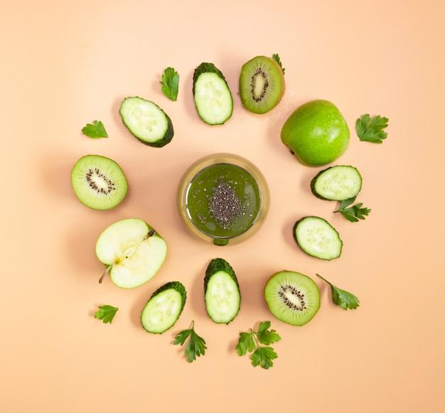 베이지색 배경에 치아씨드가 있는 유리잔에 그린 스무디. 자른 과일과 야채는 원으로 배치됩니다. 건강한 음식, 평평한 평지.