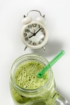 わらのクローズアップとガラスの瓶に緑のスムージー