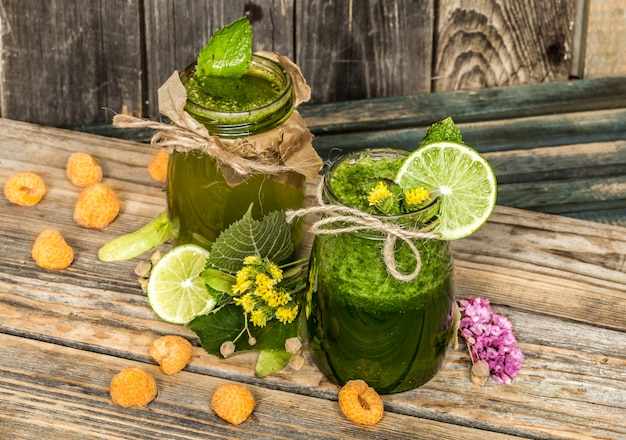 Зеленый коктейль в баночке с лаймом, киви и ягодой