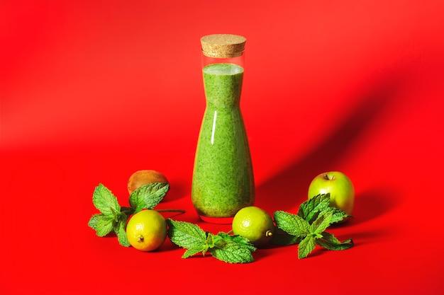 빨간색 배경에 키가 아름다운 병에 녹색 스무디