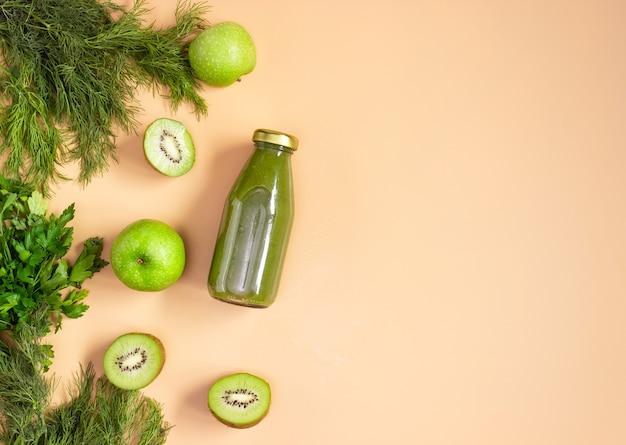 베이지색 배경에 투명한 병에 담긴 녹색 스무디. 자른 과일과 야채가 놓여 있습니다. 건강한 음식, 평평한 평지. 카피스페이스.
