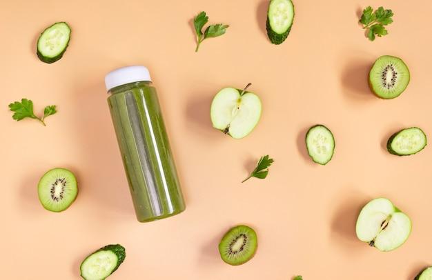 베이지색 배경에 투명한 병에 담긴 녹색 스무디. 자른 과일과 야채가 놓여 있습니다. 건강한 음식, 평평한 평지.