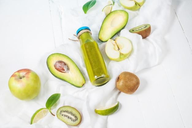 白い木製の背景にアボカド、リンゴ、キウイとボトルの緑のスムージー。