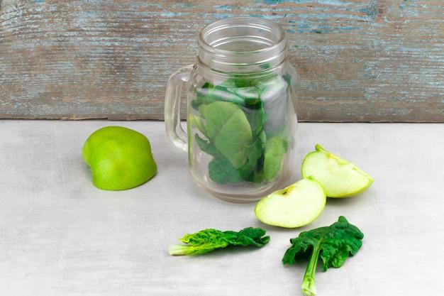 灰色の背景に新鮮な有機緑の野菜や果物とガラスの瓶の緑のスムージー。春の食事、健康的な生の菜食主義者、ビーガンの概念、デトックスの朝食、アルカリ性のきれいな食事。スペースをコピーします。