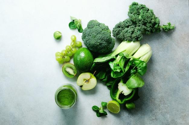 Зеленый коктейль в стеклянной банке со свежими органическими зелеными овощами и фруктами на сером