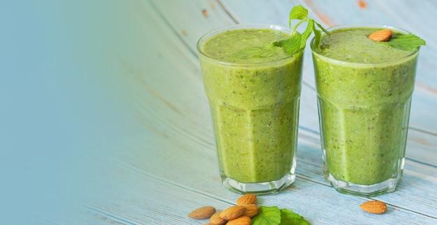 青い背景の上にガラスの緑のスムージー、ナッツ、コピースペースのあるミント-デトックス、ビーガン、ベジタリアンの健康的な野菜ドリンク