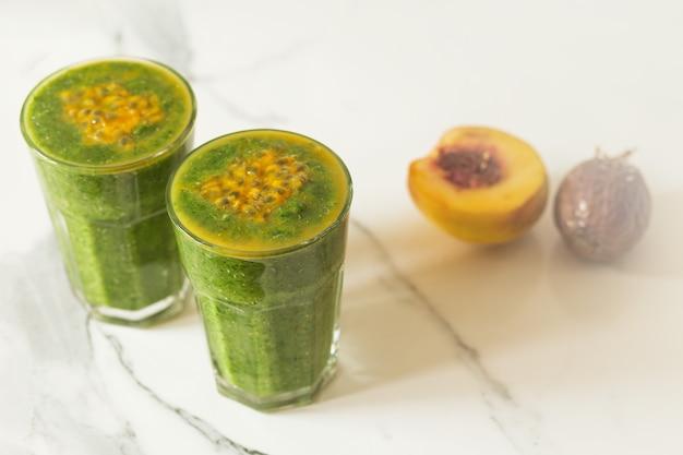 コピースペースと白い背景の上のガラスの緑のスムージー-デトックス、ビーガン、ベジタリアン健康野菜ドリンク