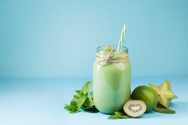 Green smoothie jar with blue background