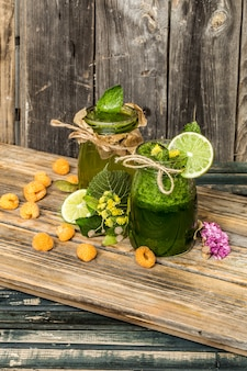 Green smoothie in a jar with lime, kiwi and berry