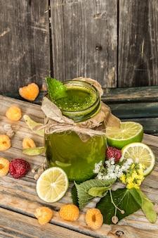Frullato verde in un barattolo con lime, kiwi e frutti di bosco
