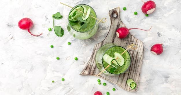 녹색 유기농 완두콩, 오이, 무, 시금치 및 라임으로 만든 녹색 스무디. 건강한 해독 음료. 평면도.